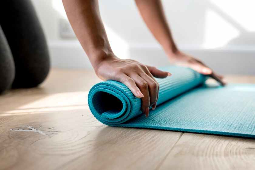 person rolling green gym mat