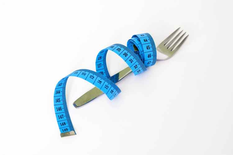 blue and black measuring tape wrapped around a silver metal fork